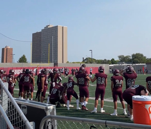 Photo of the backs of the Augsburg football team lined up on the sideline.