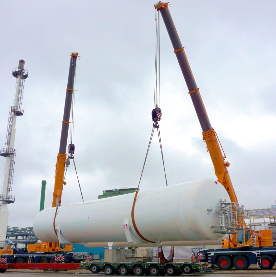 Two enormous mobile cranes lift the LH2 vessel from the truck and onto it's prepared installation site.