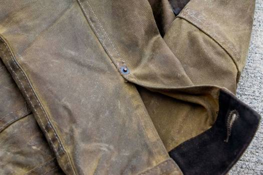 The tin cloth fabric both darkens and smooths out on areas of high abrasion (elbows, cuffs)