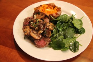 New York strip with mushrooms, spinach salad, and baked sweet potato