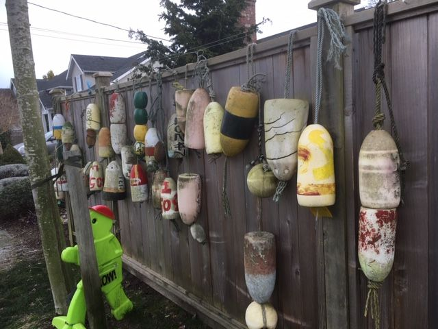A collection of buoys hanging on a fence.