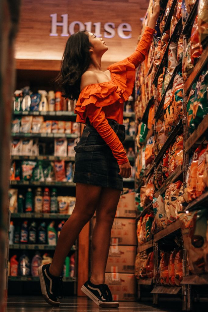 A woman reaching for a packet for crisps high up on a supermarket shelf.
