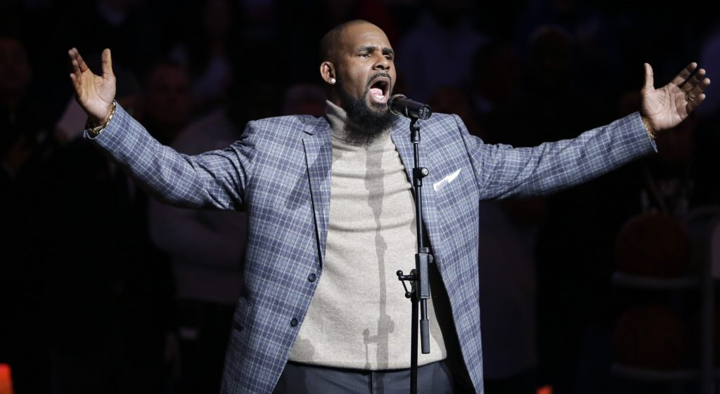 FILE - In this Nov. 17, 2015 file photo. musical artist R. Kelly performs the national anthem before an NBA basketball game between the Brooklyn Nets and the Atlanta Hawks in New York. Officials in a Georgia county want an upcoming concert by R. Kelly canceled after a media report accusing the singer of mental and physical abuse of women. The Fulton County Board of Commissioners this week sent a letter asking Live Nation, the company contracted to book events at a county-owned venue outside Atlanta, to cancel Kelly's Aug. 25, 2017 concert.(AP Photo/Frank Franklin II)