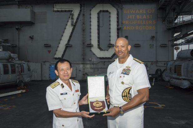 Rear Adm. John Fuller (right), commander of Carl Vinson Strike Group, accepts a plaque from Vietnamese Rear Adm. Do Quoc Viet, commander, Navy Region 3 while aboard USS Carl Vinson (CVN 70), March 6, 2018.