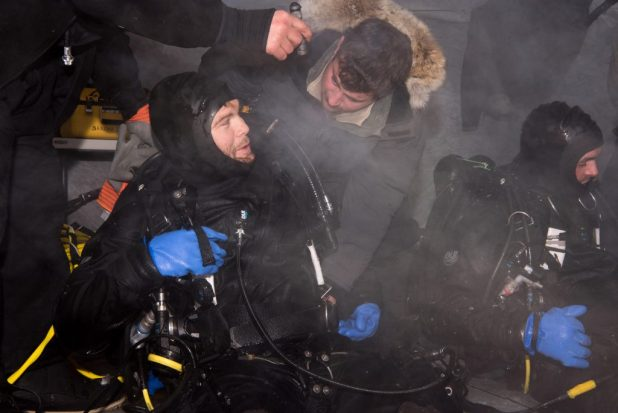 BEAUFORT SEA (March 10, 2018 Navy Diver 2nd Class Christopher Corley, left, and Navy Diver 2nd Class Owen Frederick, both assigned to Underwater Construction Team (UCT) 1, remove their diving gear following a mock torpedo recovery exercise at Ice Camp Skate in support of Ice Exercise (ICEX) 2018. (U.S. Navy photo by Mass Communication 2nd Class Michael H. Lee/Released)