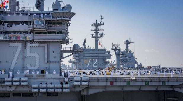 NORFOLK (April 11, 2018) Sailors aboard the aircraft carrier USS Harry S. Truman (CVN 75) man the rails during departure for the ship's regularly-scheduled deployment. (U.S. Navy photo by Mass Communication Specialist 3rd Class Joe Boggio/Released)