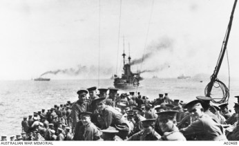 AWM A02468 -Troops of the 11th Battalion and 1st Field Company Australian Engineers assembled on the forecastle of HMS London, part of the fleet which carried the Australians from Lemnos for the Gallipoli landing at Anzac Cove. HMS Bacchante is steaming ahead. Photo taken by Ashmead-Bartlett, Ellis