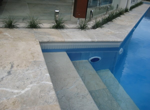 Honed Oberon marble tiles seen in a residential swimming pool as pool tiles and staircase