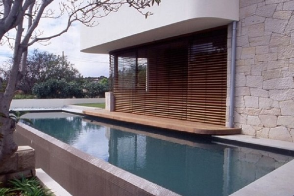 Residential stone house using Aussietecture white sandstone wall cladding with a nice swimming pool and timber floor