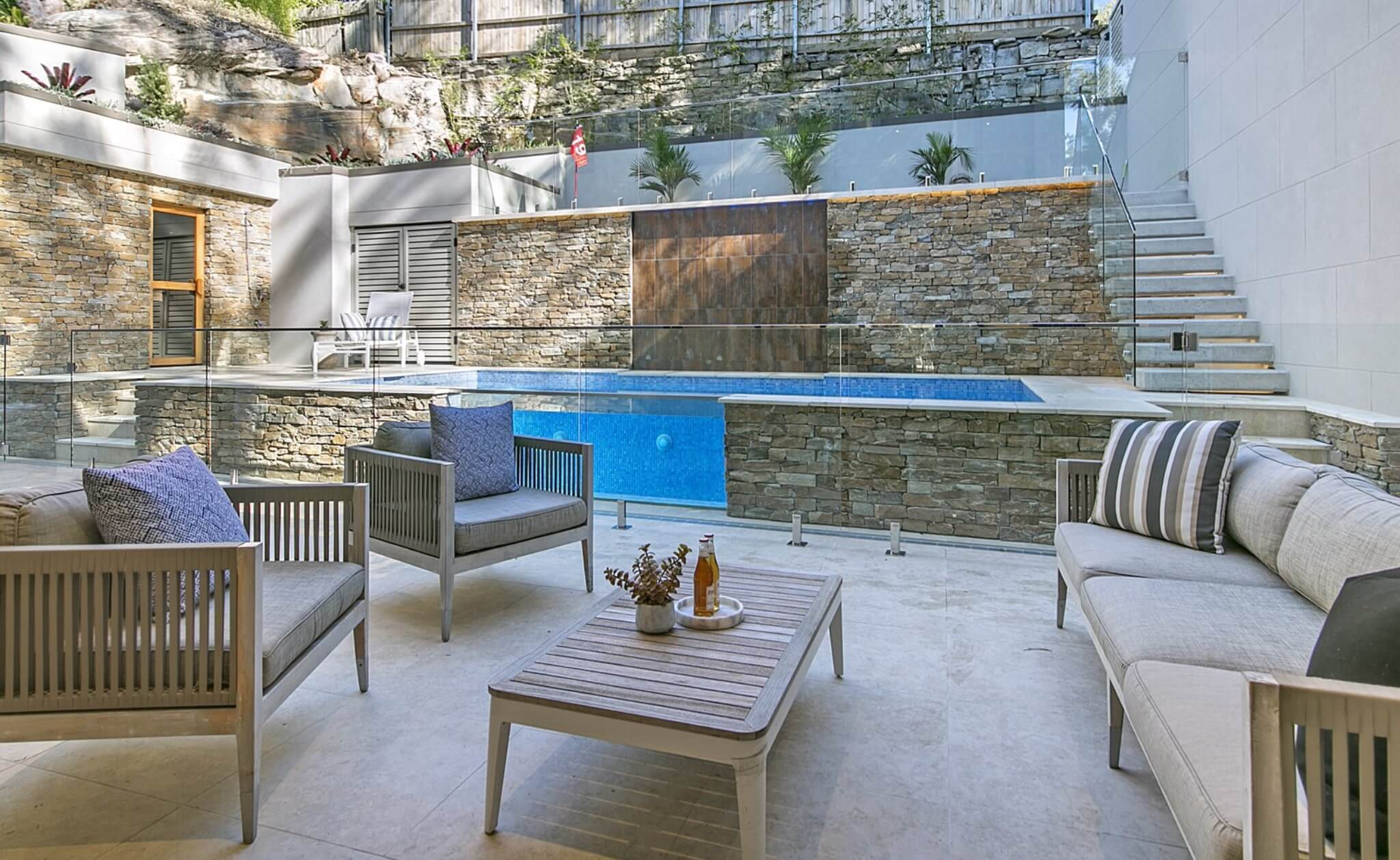 residential landscape designs using appin pavers in outdoor entertainment area with stone featured wall