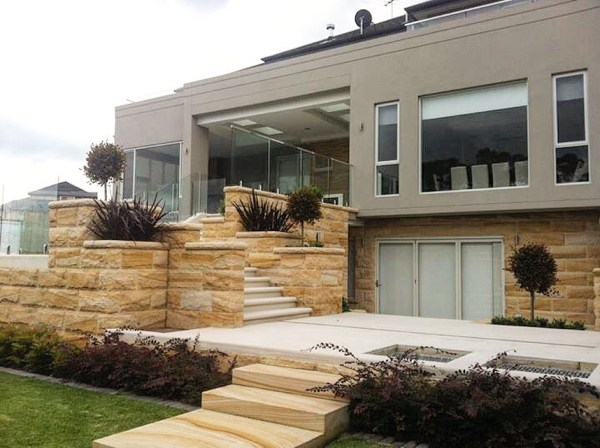 A house with rockface stone walls, stone stairs, stone capping and stone pavers
