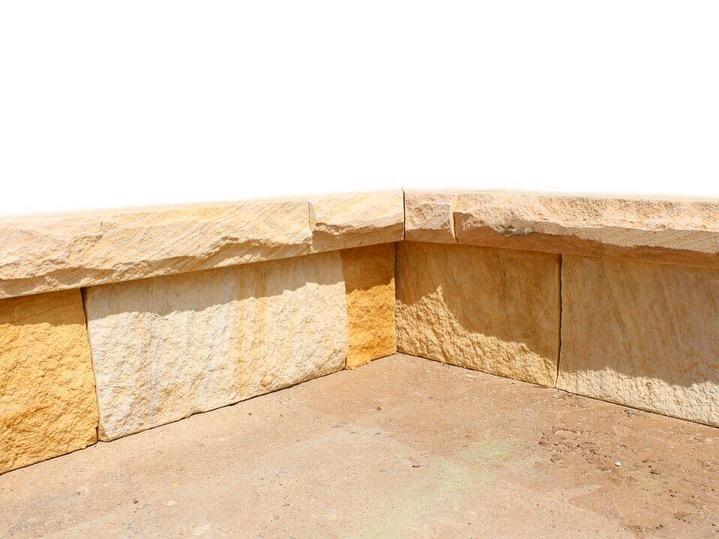 Landscape design of garden edging using sandstone blocks and capping stones