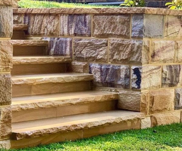 Landscape project of a garden retaining wall using ranch sandstone blocks as wall cladding, capping and stone staircase
