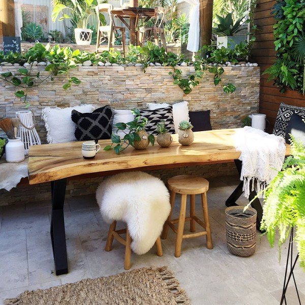 Outdoor entertaining area design of a residential house in Marrickville with a nice stone wall, cattail marble floor paver and some furniture