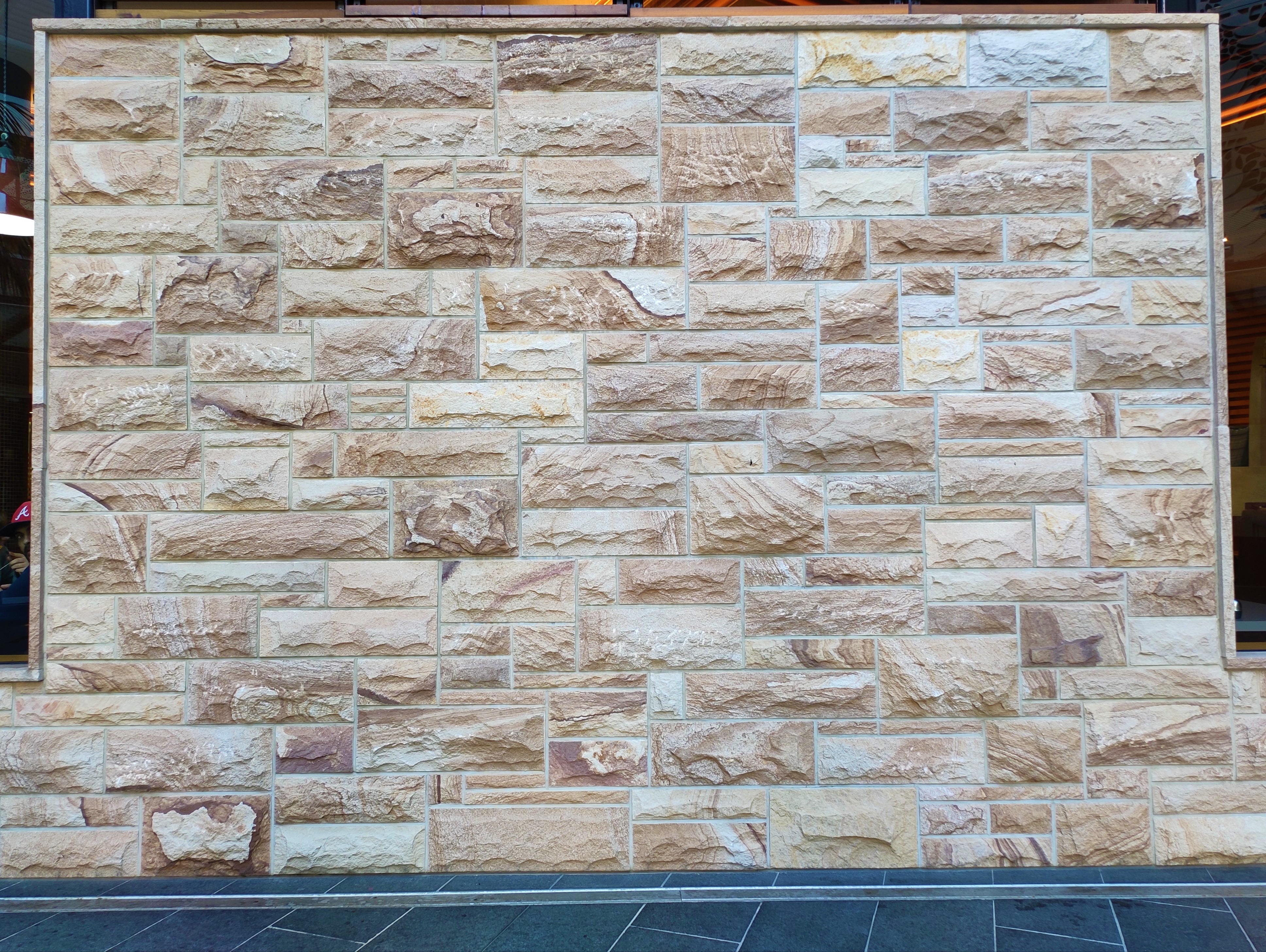 A commercial feature wall design using rockface ranch Stone walling and capping