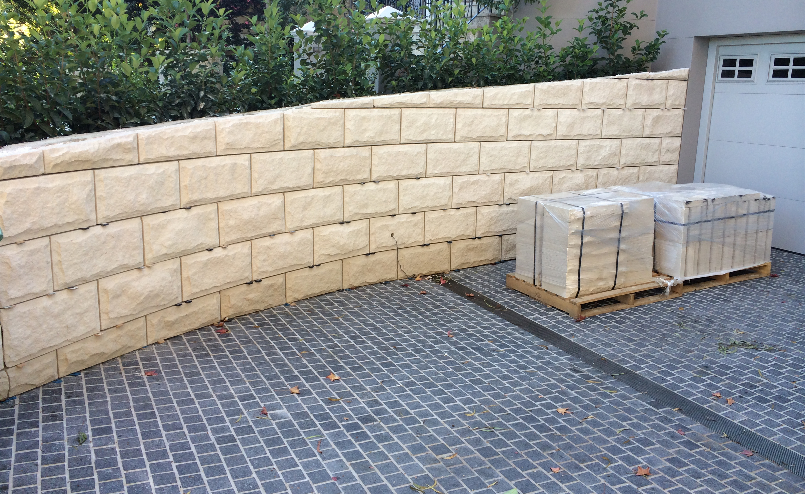 Natural stone Landscaping project of a White rockface sandstone wall with black tumbled granite stone pavers