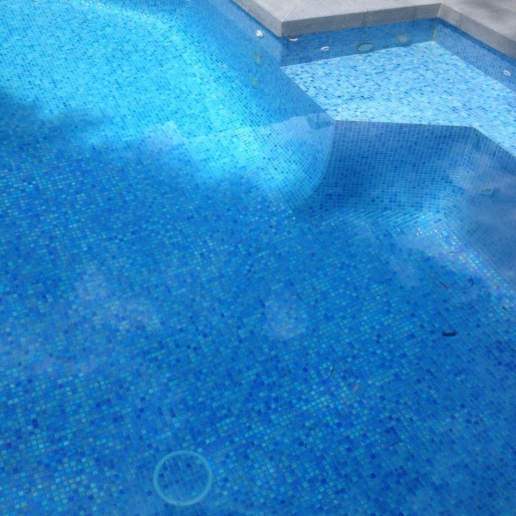 Swimming pool floor using glass mosaic tile Vegas and stone pavers