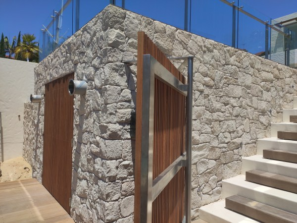 white irregular walling stone seen in a house wall application with timber door