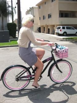"Riding her pink ""Nirve"" bike"