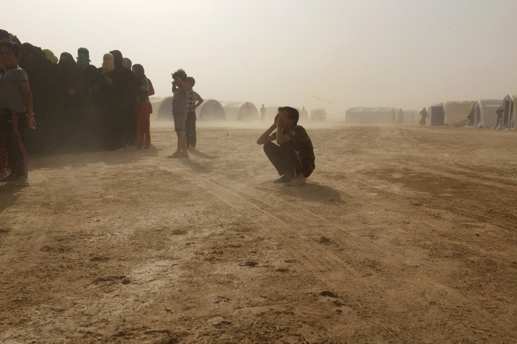 A boy crouches down during a sandstorm in a camp for families displaced from Fallujah. (Loveday Morris/The Washington Post)