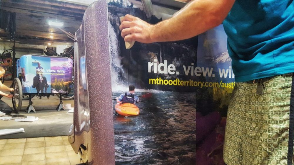 The Movemint team installing  Mt. Hood Territory ads on the Tipke fleet.