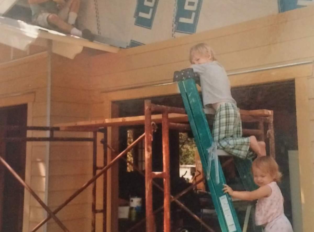 main working on woodshop child on ladder