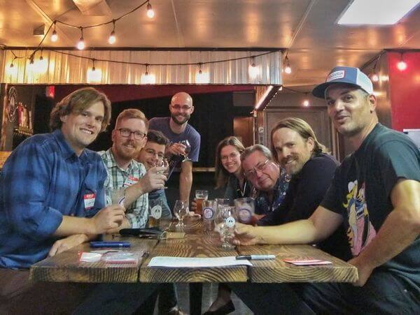 men and women around a table drinking beer talking about woodworking