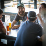 Woodworkers sitting at a table drinking beer