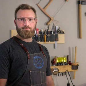 man in woodshop with apron on in front of tools