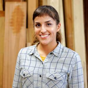 female woodworker with light colored plaid shirt in front of wood timber