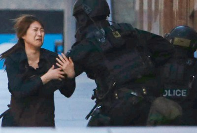 A hostage runs towards a police officer outside Lindt cafe, where other hostages are being held, in central Sydney