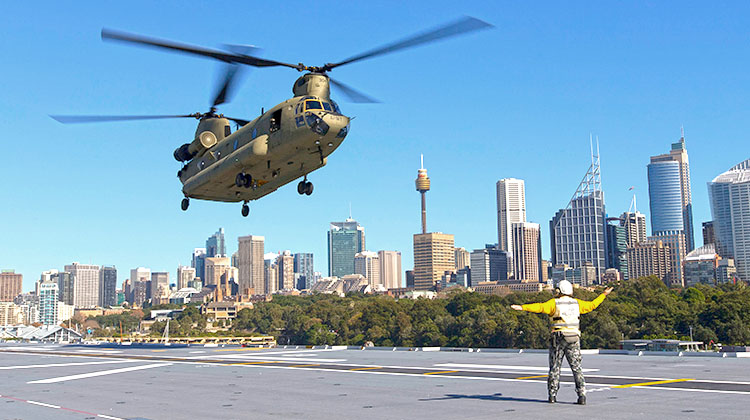 Leading Seaman Aviation Support Michael Wenzel directs a Chinook CH-47F aircraft, from the 5th Aviation Regiment in Townsville, as it lands on HMAS Canberra while the ship is alongside in her home port of Sydney.