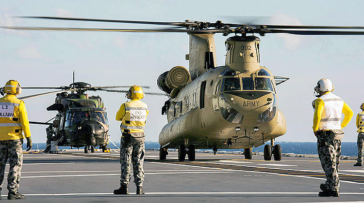 An Army MRH90 (background) and CH-47F (foreground) onboard HMAS Adelaide, as part of first of class flight trials in August 2016. (Defence)