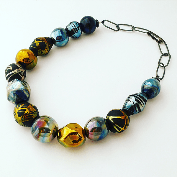 Flame worked glass beaded necklace by Jemma Clements. Gold and blue hues with six sandblasted decorative beads on sterling silver