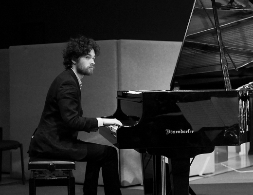 Andy Butler sitting at piano - black and white