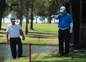 Tim Elliott takes a drop under the watchful eye of a PGA rules official