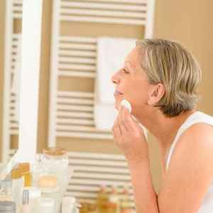 woman clean face with cotton pad