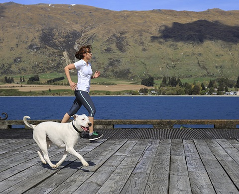 Young adult woman running with her dog
