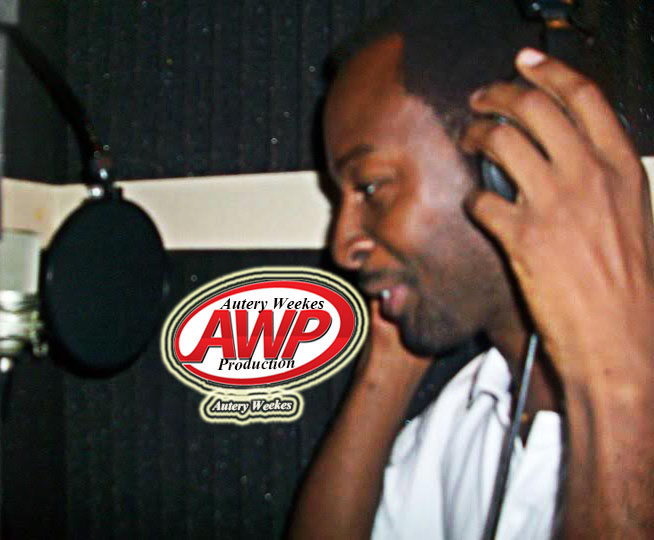 A picture with Autery Weekes in the recording booth standing in front of a studio microphone with a studio headphone over his head covering his ears.