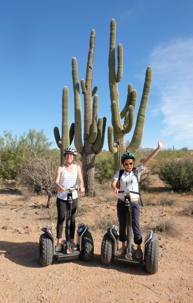 big cactus in the background and people riding Segways in the desert
