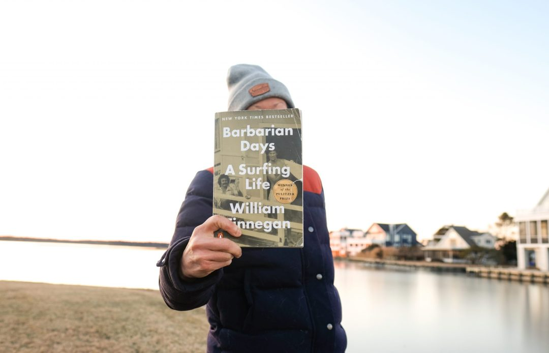 Erin McGrady holding a book at the beach