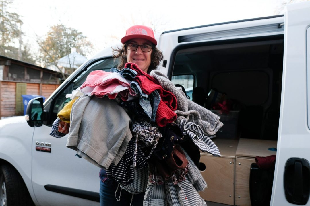 Caroline Whatley holding an armful of clothes that will be donated in an effort to downsize.