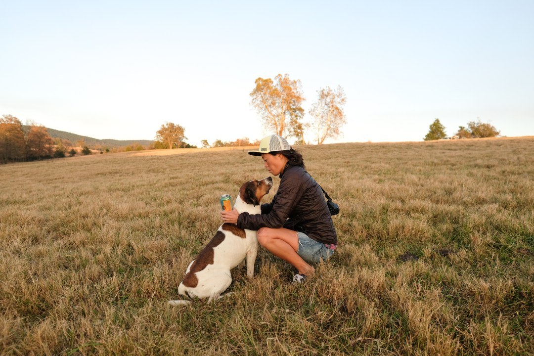 Woman and a dog in a field.