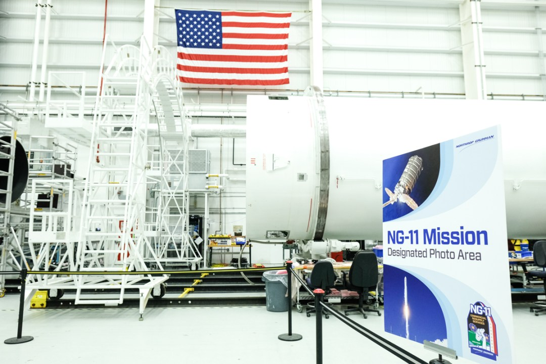 A photo of a rocket being built with an American flag in the background.
