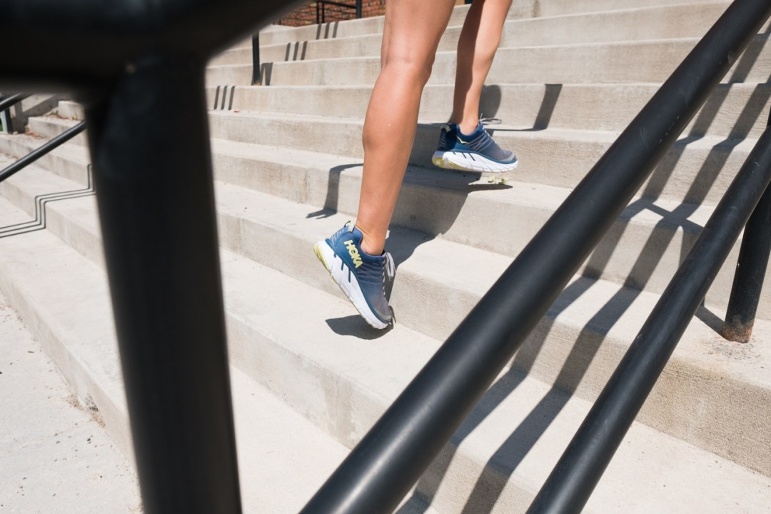 woman running up the stairs in the Hoka One One Clifton 6