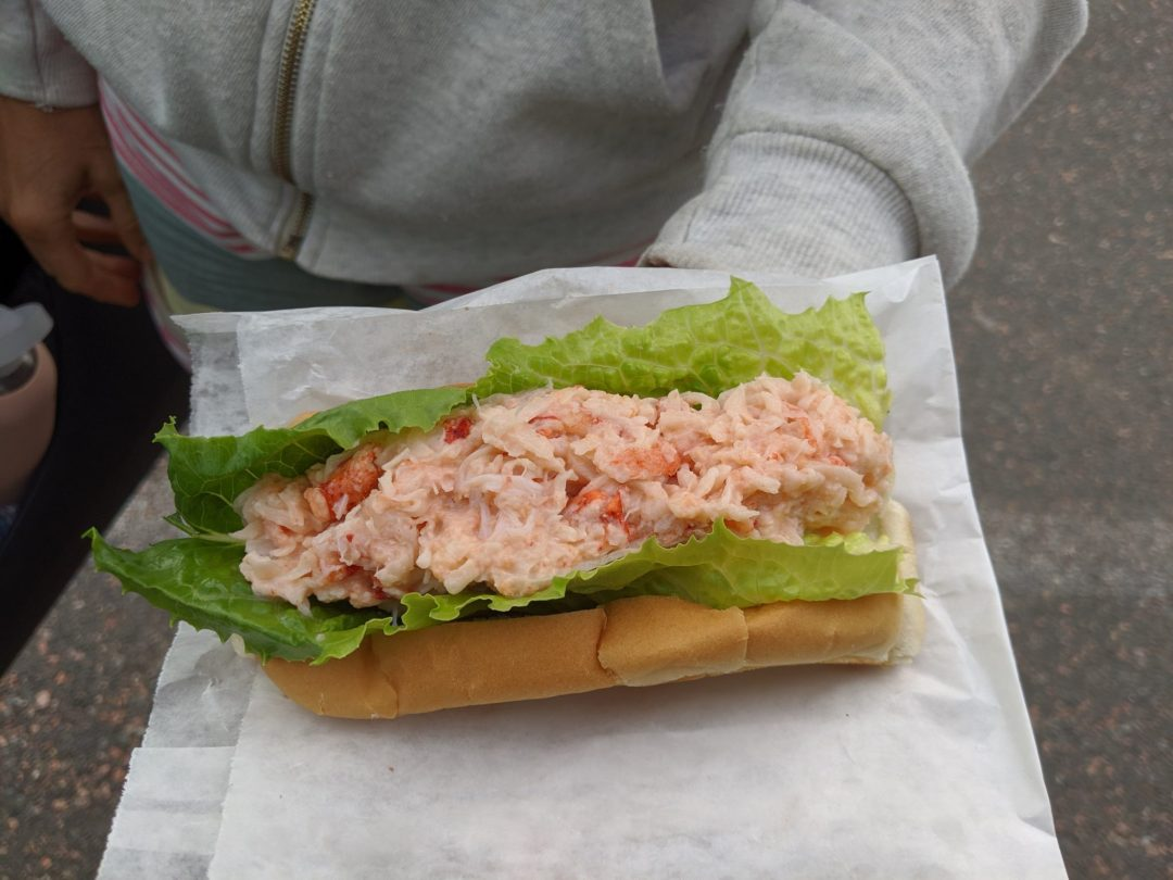 woman holding lobster roll in Nova Scotia