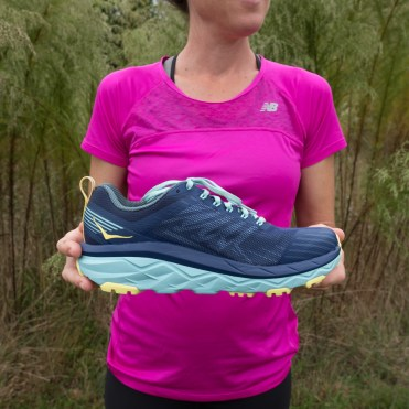 Caroline Whatley holding up the inside view of the Women's Hoka One One Challenger ATR 5