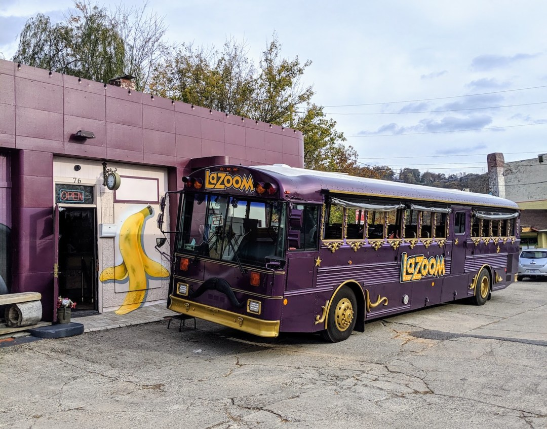 The purple Lazoom Bus in Asheville, NC parked outside of the lounge.