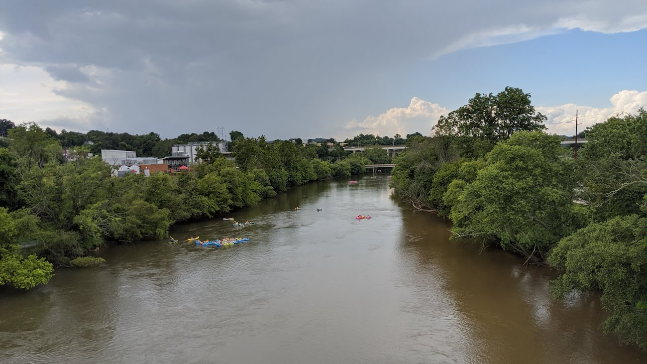 a photo of the French Broad River in the summer with tiny people tubing on it.