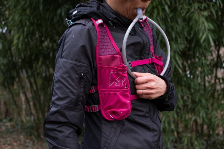 A photo of the bladder hose sternum attachment on the Nathan TrailMix 7 Liter Women's Multi-Adventure Vest which keeps your fluids easily within reach.